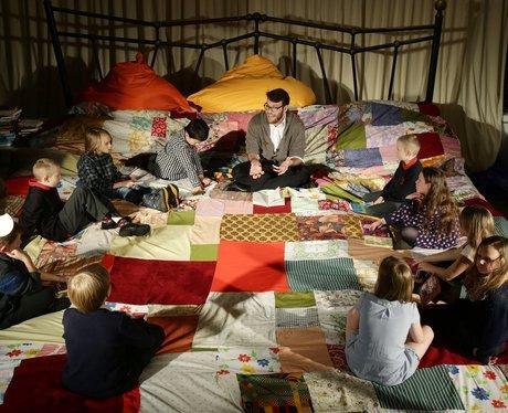 children sitting on giant bed