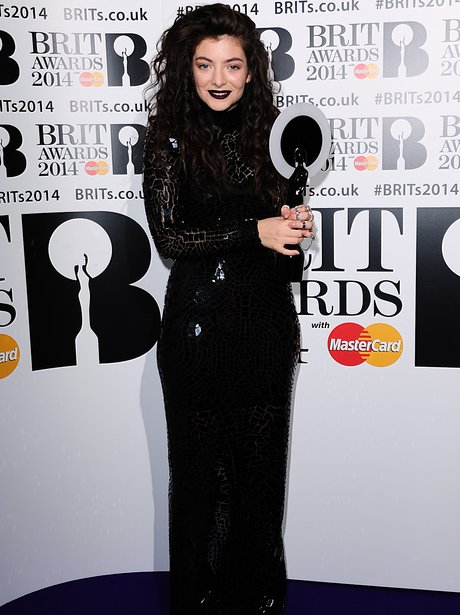 Lorde in a long black dress holding her BRIT Award