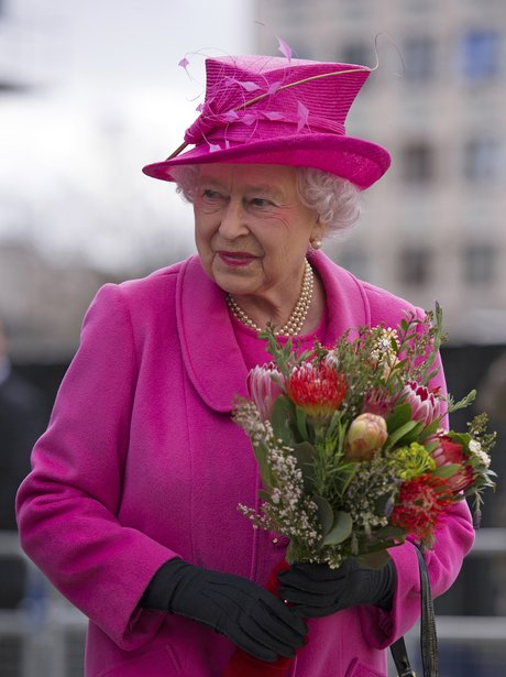 The Queen in a pink coat, holding a bunch of flowers