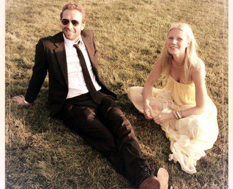 Gwyneth Paltrow and Chris Martin sit on grass
