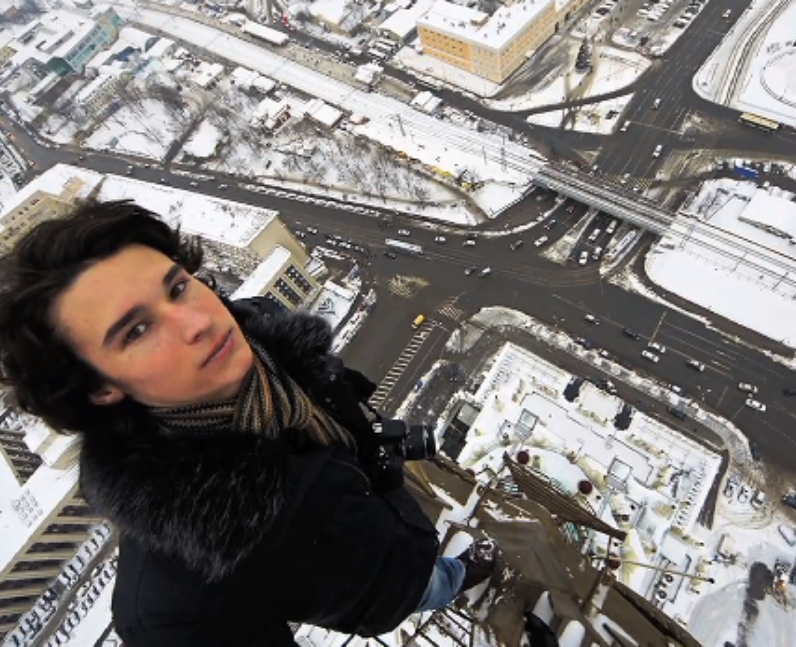 Man taking a selfie from the top of a tall buildin