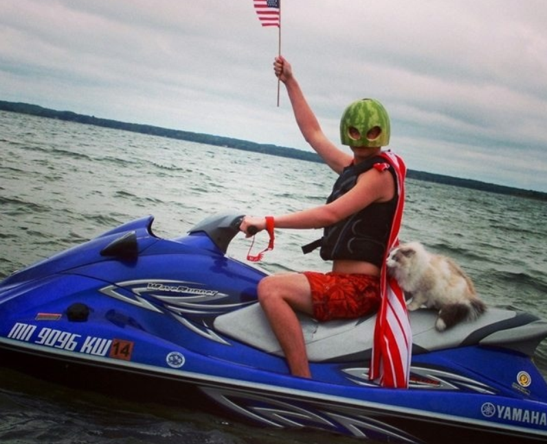 A man riding a jet ski with a cat on the back