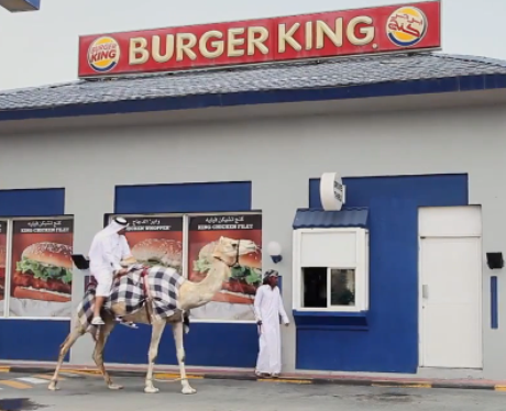 A man riding a camel outside Burger King