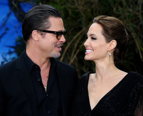 Brad Pitt and Angelina Jolie smiling at each other