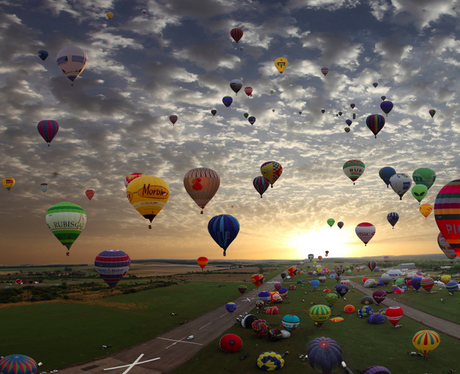 Hot air balloons filling the sky at sunset