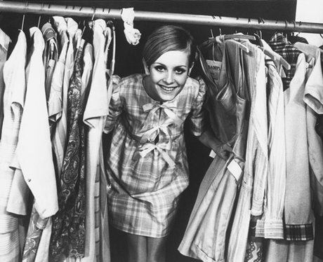 Twiggy poking out from between a clothes rack