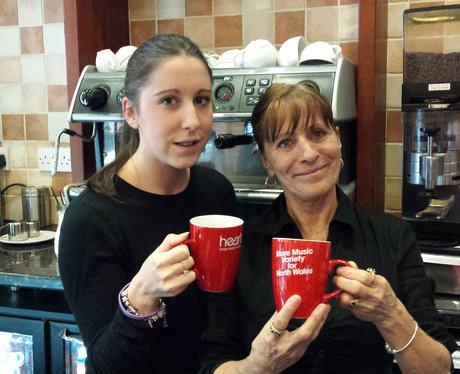 Two ladies with mugs in café.