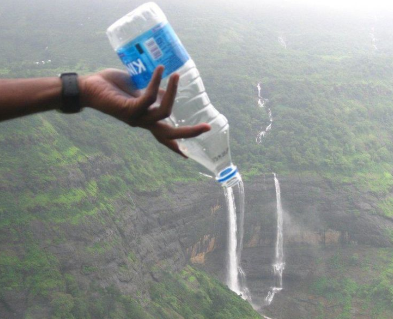 A person pouring water from a bottle.