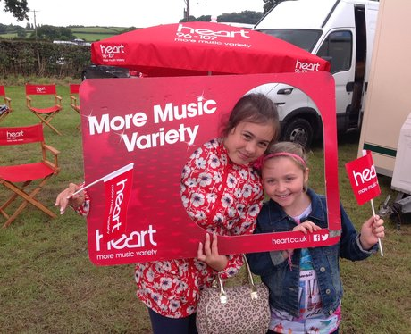 Two little girls pose with Heart frame and flags.