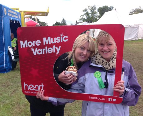 2 ladies pose with Heart frame