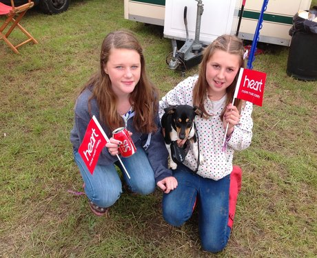 Two little girls pose with Heart flags and a dog.