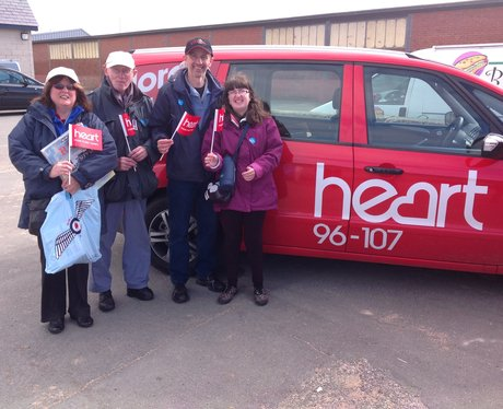 Two couples stand by Heart car waving flags.