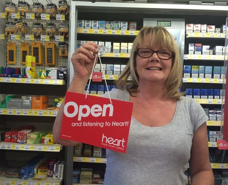 Lady in shop holding sign