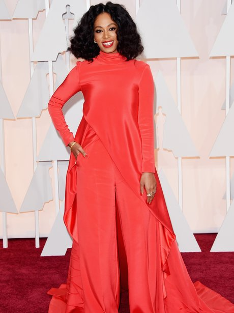 Solange Knowles in a red top and trousers