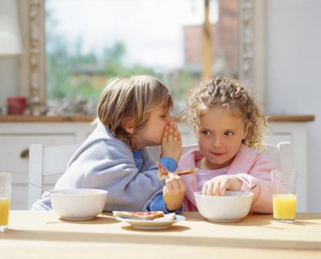 Children whispering at breakfast