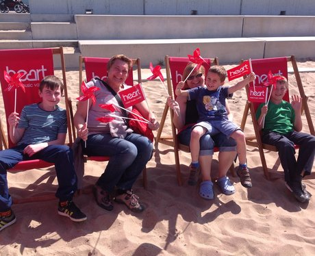 A family sitting in the deck chairs