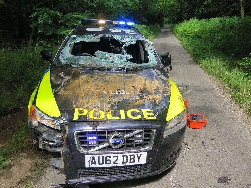 Totalled police car after dumper truck chase