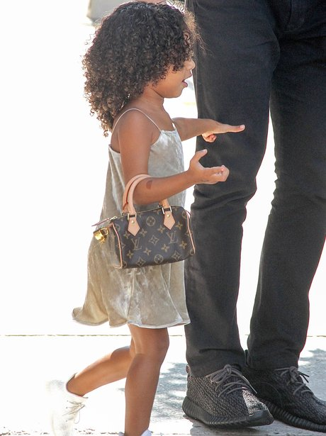 North West with a mini Louis Vuitton bag