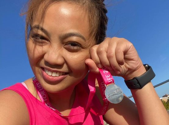 Lady holds a Race for Life Medal